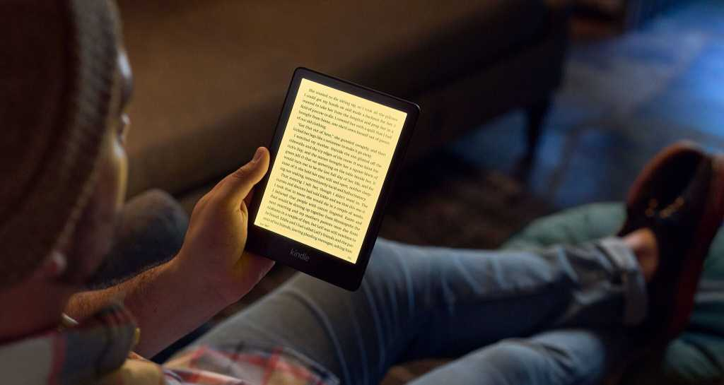 person with a hat holding a 5th generation Kindle Paperwhite