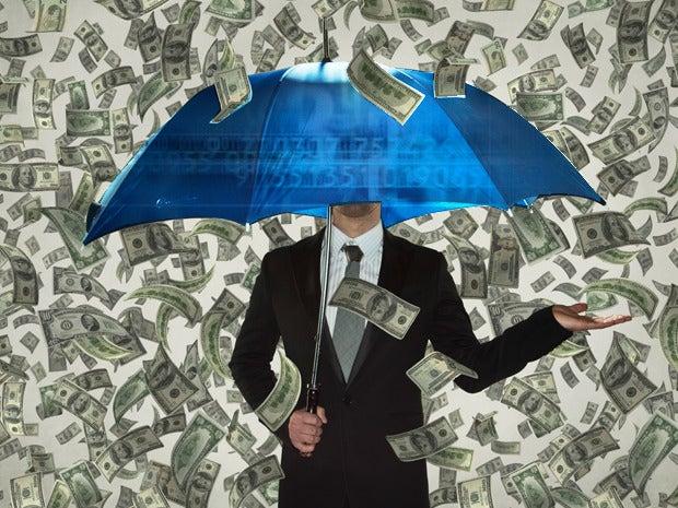 Man under umbrella raining money